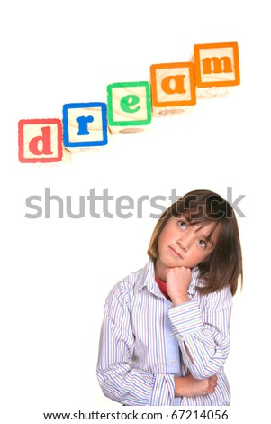 A young girl in a dreaming posture with the word dream above in blocks. - stock photo