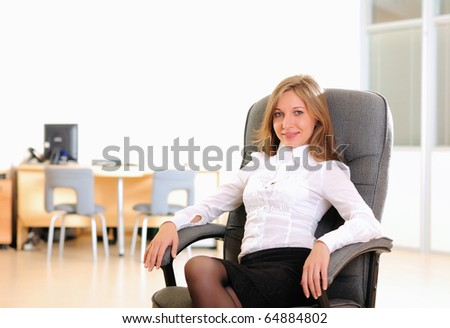A young girl in his office sits in a gray chair. - stock photo