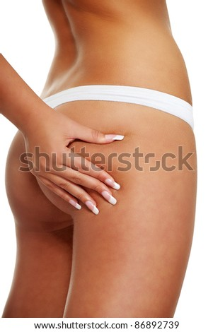A young girl in white underwear checking cellulite on her butt , isolated on a white background - stock photo