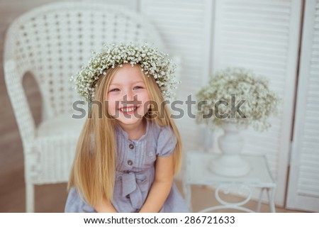 A young girl is grinning all over her face. She is wearing a light blue dress and a floral wreathe on. The armchair and flowers are behind the girl.  - stock photo