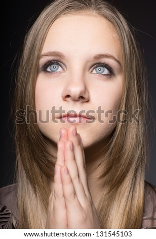 A young girl is praying to God - stock photo