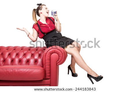 A young girl is sat on the edge of a vintage red sofa and is singing with passion and excitement - stock photo