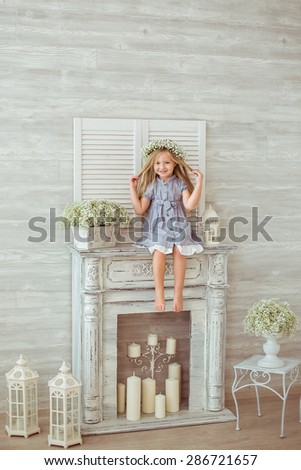 A young girl is sitting on the fireplace and tiding her hair. She is grinning all over her face. She is having a floral wreath and casual clothes on. The atmosphere of happiness is all around her. - stock photo