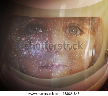 A young girl is wearing an astronaut helmet and looking into space with stars for an education, science or imagination concept. - stock photo