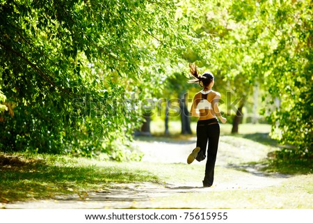 A young girl jogging in the park along trees - stock photo