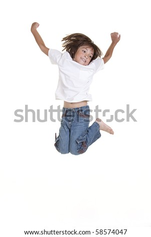 A young girl jumps up in the air in this studio image. - stock photo