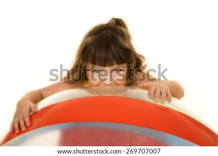 a young girl laying her face on a big beach ball. - stock photo
