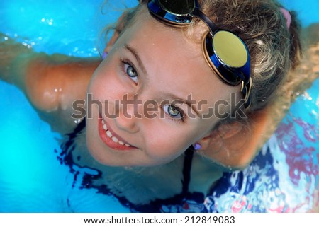 A young girl learns to swim in the pool - stock photo