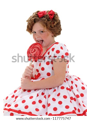 A young girl licks a red lollipop isolated on white - stock photo