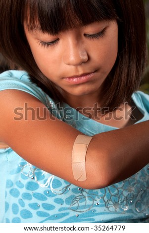 a young girl looks at her bandage with the focus on her bandage - stock photo