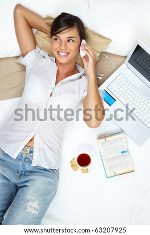 A young girl lying in bed and talking on her mobile phone - stock photo