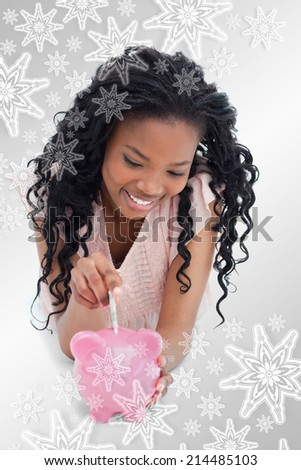 A young girl lying on the floor putting money into a piggy bank against snowflakes on silver - stock photo