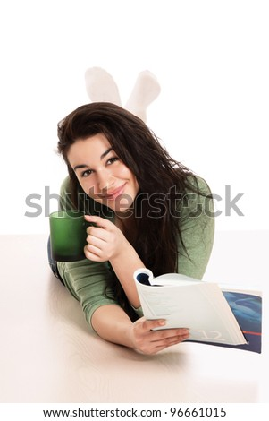 A young girl lying on the floor with a book and a cup of tea, isolated on white background - stock photo