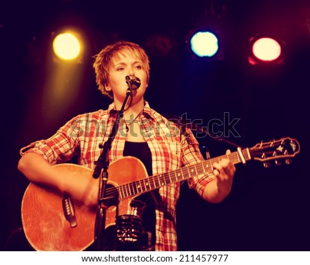 a young girl playing a guitar on a stage toned with a retro vintage instagram filter - stock photo