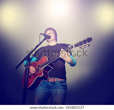 a young girl playing a guitar on a stage toned with a retro vintage instagram filter effect app or action  - stock photo
