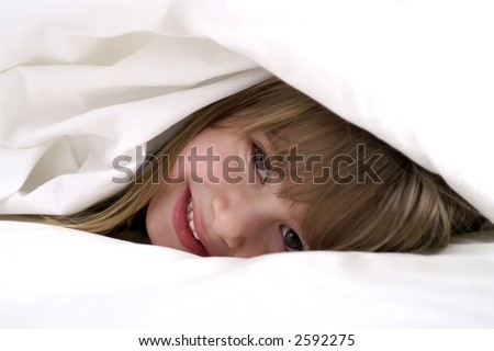 A young girl playing in the sheets - stock photo