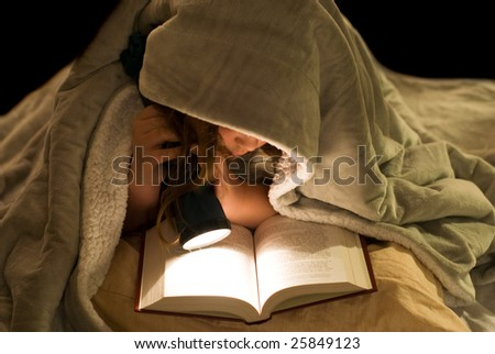 A young girl reading a book under the covers with a flashlight - stock photo