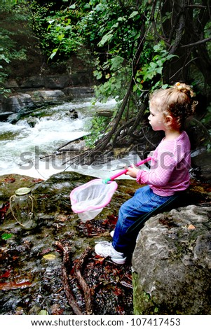 A young girl reflects on the beauty surrounding her as she sits on a rock alongside a flowing creek, taking a break from filling her collection jar with crawdads, tadpoles or other bits of nature. - stock photo