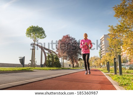 A young girl running outdoors in city - stock photo