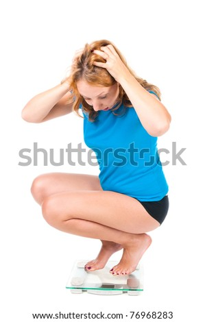 A young girl screams as she sees her weight on the scale - stock photo