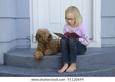 A young girl sitting on the front steps is engrossed in a book as her dog sits beside her - stock photo