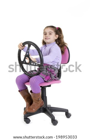 a young girl sitting with a steering wheel - stock photo