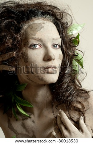 a young girl, smeared with clay - stock photo