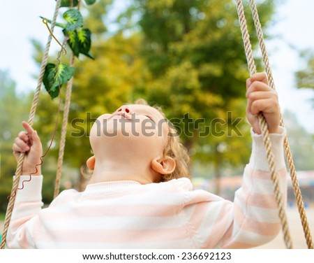 A young girl smiling on a swing - stock photo