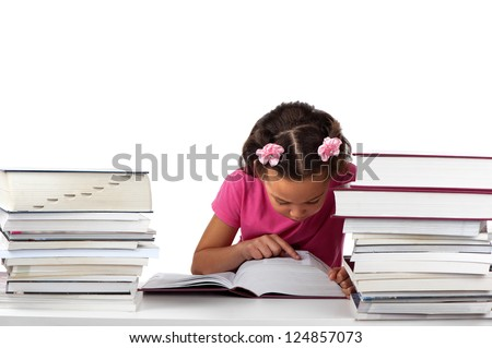 A young girl stays focused whilst reading a huge book in the midst of other reading material. - stock photo