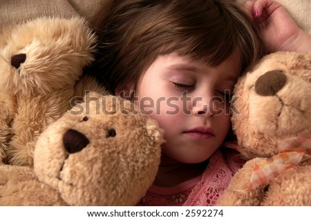 A young girl takes a nap with her teddy bears - stock photo