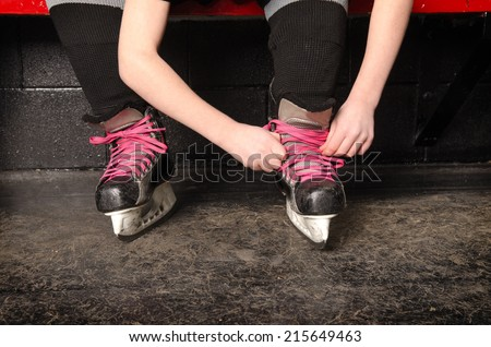 A Young Girl Ties Her Ice Hockey Skates in the Change Room of the Rink - stock photo