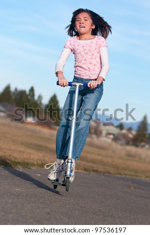 A young girl tries jumping on a small scooter. - stock photo