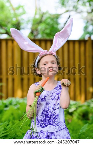 A young girl wearing Easter bunny ears holds a fresh carrot in her hand while posing like a bunny outside in a lush garden setting during the spring season.  Part of a series.  - stock photo
