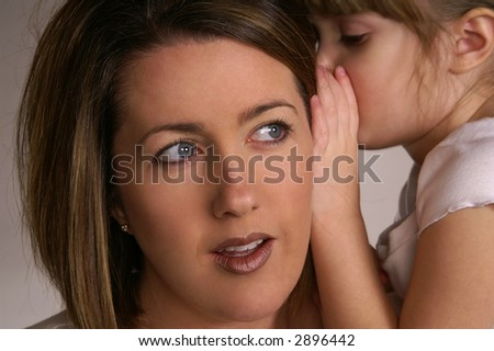 A young girl whispering secrets in her mommy's ear - stock photo