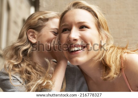 A young girl whispering something into another girls ear. - stock photo