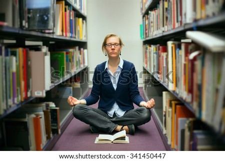 A young girl with a book in the library meditates for exams - stock photo