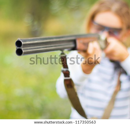 A young girl with a gun for trap shooting and shooting glasses aiming at a target. Short depth of field, focus on the barrel - stock photo
