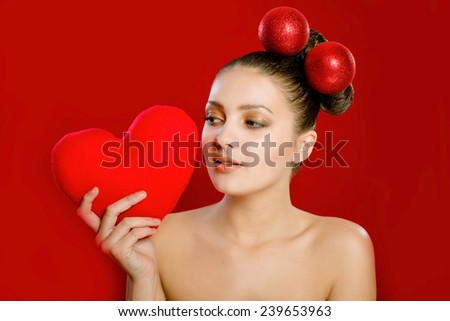 A young girl with a red heart toy in her hands - stock photo