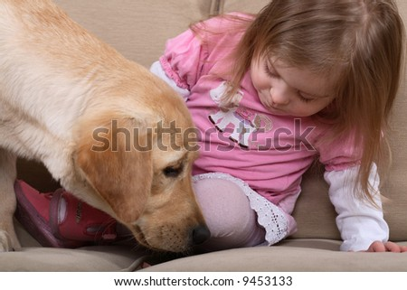 A young girl with Down Syndrome sitting on a couch with a puppy. A form of therapy. - stock photo
