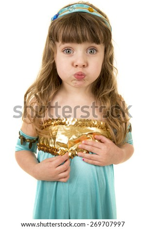 A young girl with her cheeks puffed out looking. - stock photo