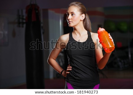 A young girl with water after training, in gym - stock photo
