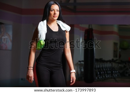 A young girl with water after training with a towel on her neck. In gym - stock photo