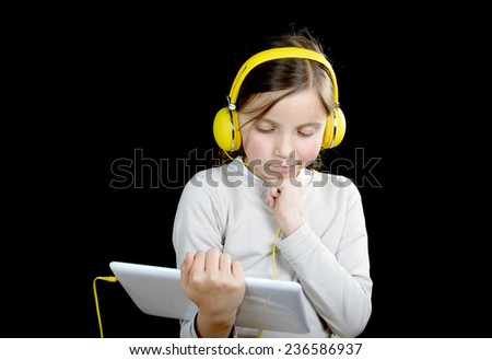 a young girl with yellow  headphones and a digital tablet listen music - stock photo