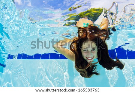 A young girls shows her face underwater - stock photo