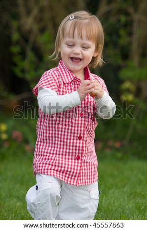 A young gril is laughing outdoors. - stock photo