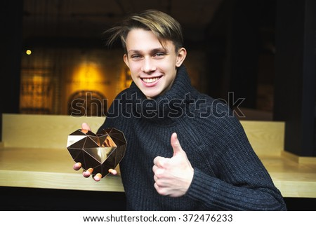 a young guy holding a heart. Golden heart - stock photo
