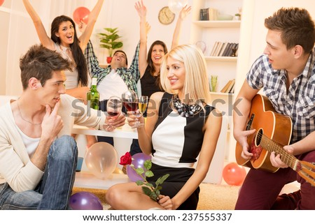 A young guy is courting the pretty girl at home party, while their friend plays acoustic guitar, and in the background the rest of society with arms raised celebrated their relationship. - stock photo