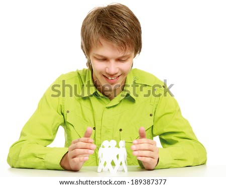 A young guy sitting at the desk, holding paper people - stock photo