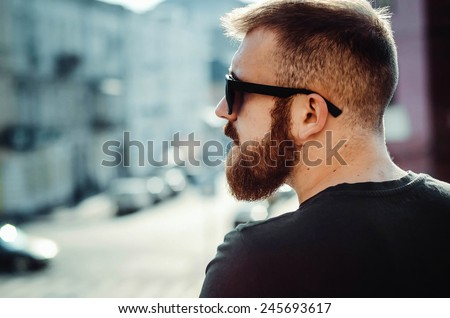 a young guy with a beard and glasses on the street - stock photo