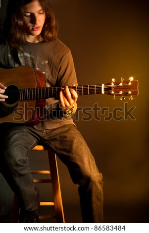 A young guy with long hair playing an acoustic guitar with golden light - stock photo